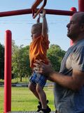 Little boy and his daddy on playground equipment. royalty free stock images