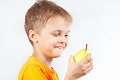 Little boy in orange shirt with ripe yellow pear Stock Photos