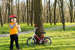 Little boy out riding stopping for a drink. Little boy out riding his bicycle stopping amongst the trees in a wooded park for a drink of water from a plastic Stock Photography
