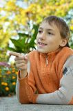 Little boy outdoors. In autumn,shows on something Royalty Free Stock Photo