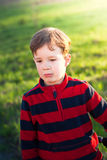 Little boy outdoors. A charming little boy outdoors on grass background Royalty Free Stock Photo