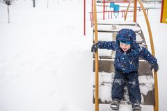 Little boy outdoors in cold winter snow. playground. Little boy outdoors in cold winter snow. Winter playground Stock Photos