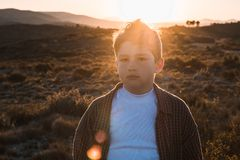 Little boy outdoors looking at the camera with serious expression. Kid in a sunset. Portrait of a little boy outside looking at the camera with serious royalty free stock photos