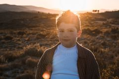 Little boy outdoors looking at the camera with serious expression. Kid in a sunset. Portrait of a little boy outside looking at the camera with serious stock photo