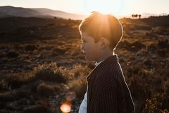 Little boy outdoors looking at the camera with serious expression. Kid in a sunset. Portrait of a little boy outside looking at the camera with serious royalty free stock image