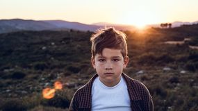 Little boy outdoors looking at the camera with serious expression. Kid in a sunset. Portrait of a little boy outside looking at the camera with serious stock image