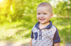 Little boy outdoors. Portrait of a laughing little boy outdoors. Walk in nature with sunlight Royalty Free Stock Photo