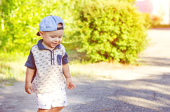 Little boy outdoors. Little boy wearing a cap during outdoor movement. Walk in nature with sunlight royalty free stock photo