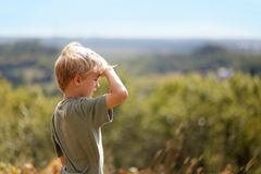Little Boy Outside on Hike Looking out over Trees on Bluff. A little 8 year old boy out on a nature hike, is sheilding his eyes from the sun as he looks out over Stock Images