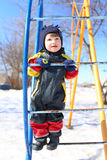 Little boy in overall plays on climber in winter Stock Image