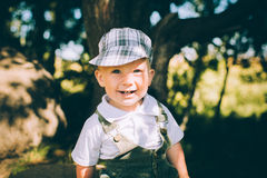The little boy in overalls and a cap Stock Images