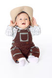 Little boy in overalls sitting and holds hands a hat Stock Photos