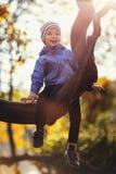 Little Boy på en trädfilial behandla som ett barn klättringar ett träd royaltyfri fotografi