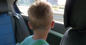 Little Boy på ett bilbaksäte lager videofilmer