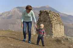 A little boy with a pacifier travels with his mother, walking among the ancient Ossetian buildings. stock photo