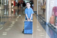 Little boy with the packages in the shop Royalty Free Stock Images