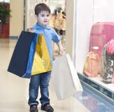 Little boy with the packages in the shop Royalty Free Stock Photo