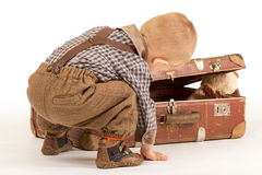 Little boy is packing his suitcase. Little boy is packing his old brown suitcase to go into the world Royalty Free Stock Photos