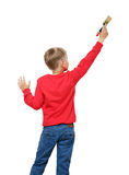Little boy with paintbrush on wall, back view Royalty Free Stock Images
