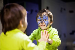 Little boy with painted face as butterfly, looking at the mirror Stock Image