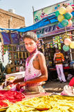 Little boy with a painted face selling paint colors for the Holi Royalty Free Stock Photography