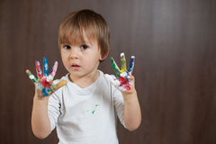 Little boy with painted hands. Little boy with colorful painted hands Royalty Free Stock Photography