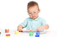 Little boy painting. With colorful paint, wearing glasses and look concentrate Royalty Free Stock Images