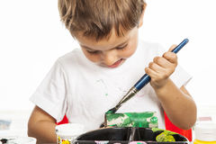 Little boy painting. A concentrated child painting a cardboard tube Royalty Free Stock Image