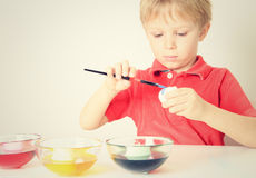 Little boy painting eggs for easter Stock Image