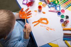 Painting little boy. Little boy painting with gouache on hand, top view Royalty Free Stock Photos