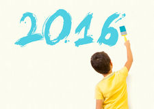 Little boy painting new year 2016 with brush on the wall Stock Photos