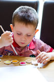Little boy painting a picture. Young boy painting a picture with a paintbrush Royalty Free Stock Image
