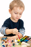 Little boy painting the stones with watercolor Stock Images