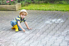 Little boy painting a tractor vehicle with chalk in summer Royalty Free Stock Image