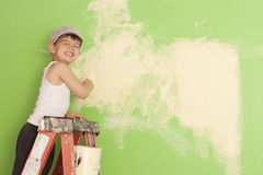 Little boy painting the wall. Young boy standing on a ladder painting a wall. Boy is on the left with plenty of wall space for design or text purposes royalty free stock image
