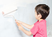 Little boy painting wall white color Stock Images