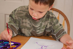 Little Boy Painting with Watercolors. This little boy is enjoying a creative moment while painting with watercolors at a table as a future young artist Royalty Free Stock Photo