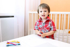 Little boy painting with wax pencils Royalty Free Stock Images
