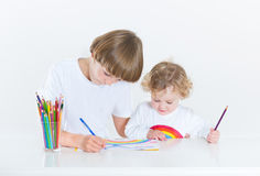 Little boy painting at white desk with toddler sister Royalty Free Stock Image