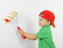 Little boy with paintroller on white wall. Little boy with paintroller in hands near white wall Royalty Free Stock Photography