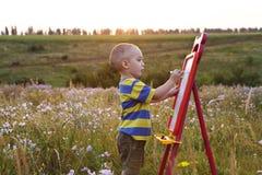 Little boy paints on a canvas , landscape outdoors Royalty Free Stock Photos