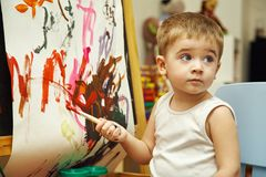 Little boy paints a on easel Royalty Free Stock Photography