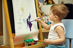 Little boy paints a on easel Royalty Free Stock Photo
