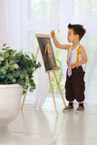 A little boy paints on an easel in the room Stock Photography