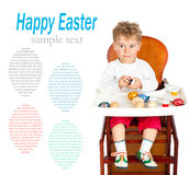 Little boy paints Easter eggs Stock Photos