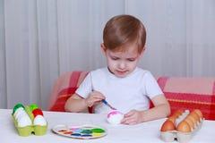 Little boy paints eggs stock images