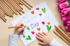 Little boy paints greeting card for Mom on Mother`s Day with the inscription `Happy mother`s day`. Top view Stock Image