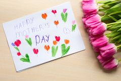 Little boy paints greeting card for Mom on Mother`s Day with the inscription `Happy mother`s day`. Top view Stock Photos