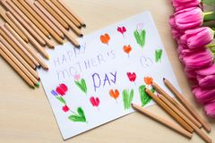 Little boy paints greeting card for Mom on Mother`s Day with the inscription `Happy mother`s day`. Top view Royalty Free Stock Image