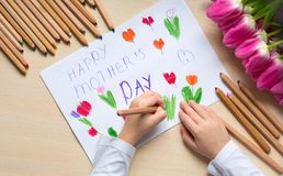 Little boy paints greeting card for Mom on Mother`s Day with the inscription `Happy mother`s day`. Top view Stock Photo
